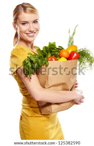 woman holding a shopping bag full of groceries, mango, salad,  radish, lemon, carrots on white background
