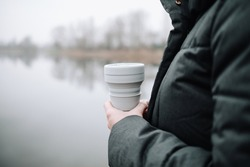 Woman holding a silicone collapsible cup, reusable coffee tumbler.