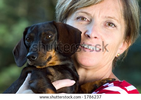 Woman holding a small dog. Focus on woman's face.