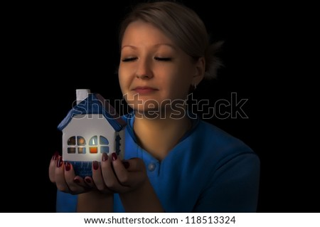 woman holding a small house