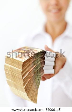 Woman holding a stack of euro banknotes - extreme shallow depth