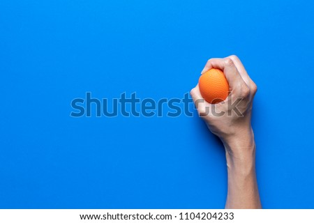 woman holding a stress ball in her hand on blue background Сток-фото ©