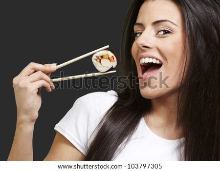 woman holding a sushi piece with chopsticks against a black background