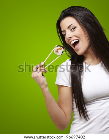 woman holding a sushi piece with chopsticks against a green background