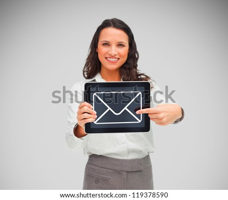 Woman holding a tablet pc smiling and pointing at message symbol on screen - stock photo