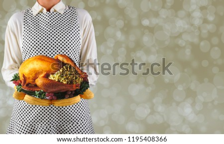 Woman holding a Thanksgiving turkey on a platter over a warm bokeh background, with room for your copy.