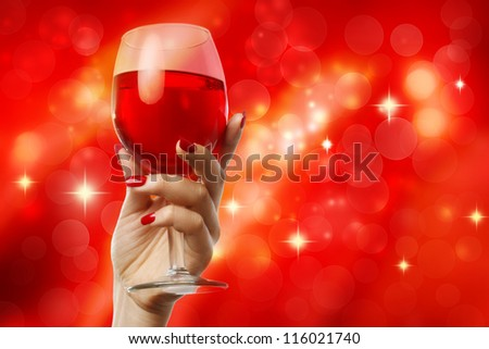 Woman holding a wine glass on a red abstract background