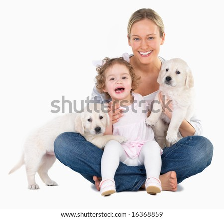 Woman holding a young girl and two puppies Happiness family and friendship