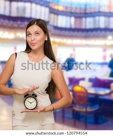 Woman Holding Alarm Clock and looking up at a restaurant
