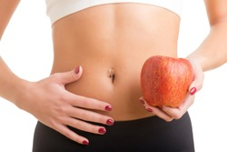 Woman holding an apple with a hand on her abdomen. Focus on the apple.