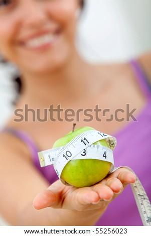 Woman holding an apple with a measure tape around it - stock photo