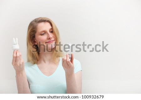 Woman holding an eco-friendly spiral fluorescent bulb in one hand looks at an old inefficient incandescent bulb in her other hand with regret as she makes her choice