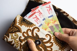 Woman Holding and Showing 75.000 Banknote Indonesian Rupiah Money in Traditional Wallet