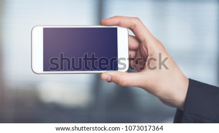 Woman holding and showing mobile phone