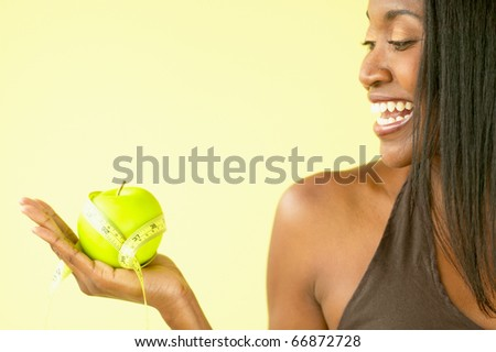 Woman holding apple and tape measure - stock photo