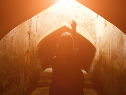 Woman holding arms hands in praying position in a sacred place.