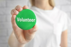 Woman holding badge with word VOLUNTEER on light background