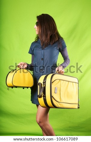 woman holding baggage on green background wall