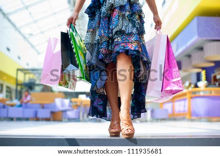 woman holding bags in shopping mall