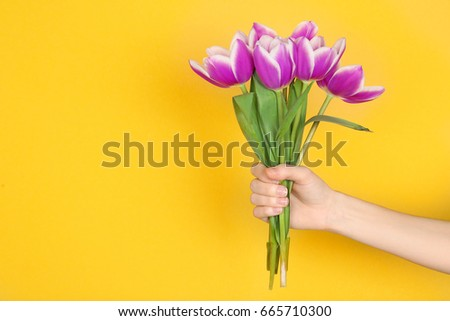 Woman holding beautiful lilac tulips on color background