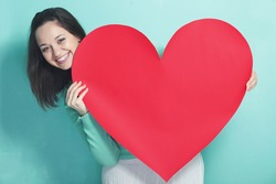 Woman holding big red heart on blue aqua background