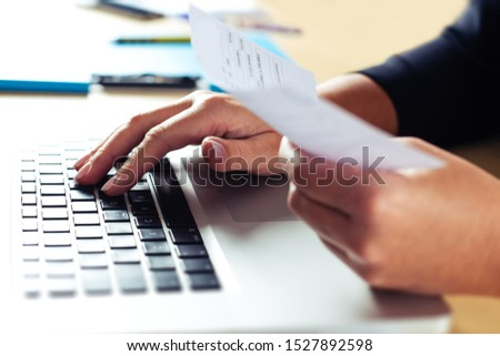 Woman holding bills and paying bills on computer