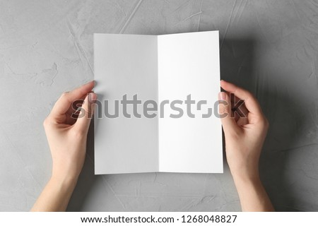 Woman holding blank brochure mock up on light background, top view #1268048827