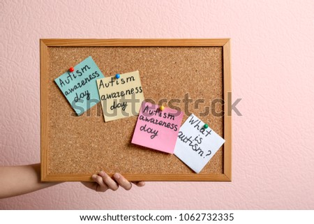 Woman holding board with autism related phrases on color background #1062732335