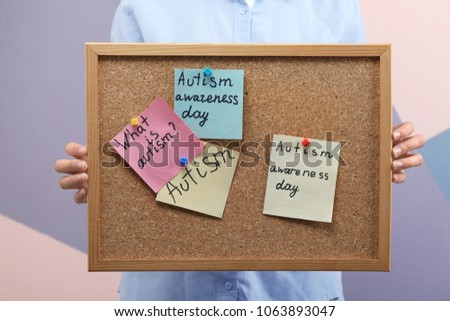Woman holding board with phrases about autism on color background #1063893047