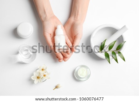 Woman holding bottle of cream over table with cosmetic products