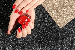 Woman holding bottle of red nail polish in manicured hand on color background, top view. Space for text