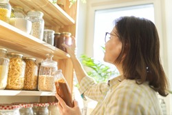 Woman holding bottle with ketchup, picking food from storage cabinet in kitchen, storage with wooden shelves