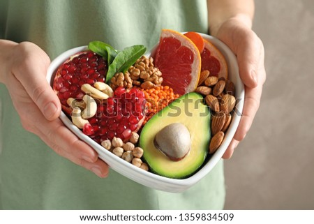 Woman holding bowl with products for heart-healthy diet, closeup