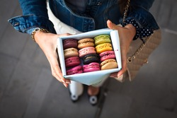 Woman holding box with colourful macaroons. Dessert. Summer travel vacation in French Riviera.