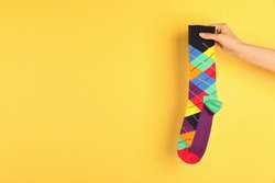 Woman holding bright sock and space for design on color background
