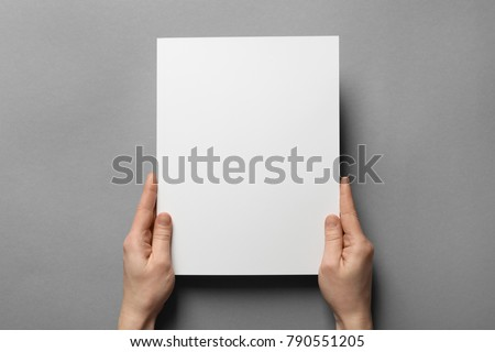 Woman holding brochure with blank cover on grey background. Mock up for design