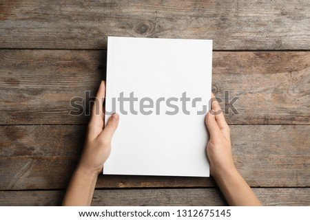 Woman holding brochure with blank cover on wooden background, top view. Mock up for design #1312675145