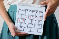 Woman holding calender with marked missed period. Unwanted pregnancy, woman's health and delay in menstruation. Period late