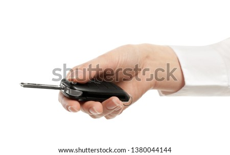 Woman holding car key isolated on white