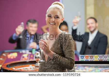 Woman holding champagne glass as people are cheering behind her in casino
