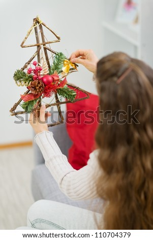 Woman holding Christmas decoration tree. Rear view - stock photo