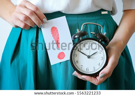 Woman holding clock at belly. Missed period, unwanted pregnancy, woman's health, period late and delay in menstruation.