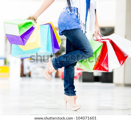 Woman holding colorful shopping bags at the mall