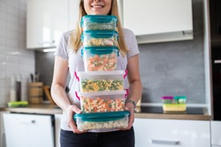 Woman holding containers with frozen mixed vegetables.