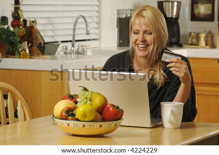 Woman holding credit card in her kitchen Using her Laptop for Ecommerce.