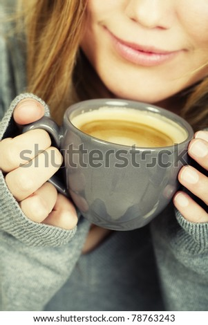 woman holding cup of coffee and smiles
