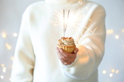 Woman holding cupcake with burning sparklers against blurred festive lights, closeup