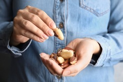 Woman holding delicious Brazil nuts, closeup view