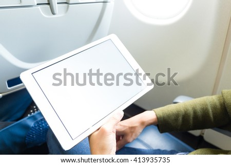 Woman holding digital tablet at airplane