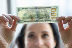 Woman holding dollar bill and looking at it with watermarks closeup. Counterfeiting money concept